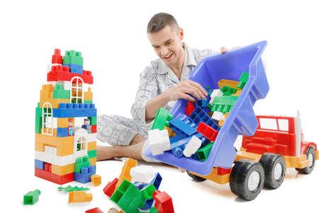 erwachsene: Big Baby. Aufgeregte junge Mann im Schlafanzug spielen Spielzeug während auf weiß isoliert Lizenzfreie Bilder