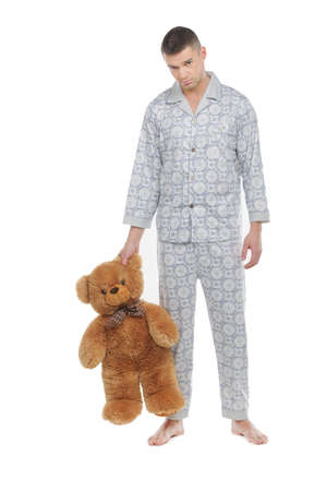 one adult: Man with teddy bear. Young man in pajamas holding teddy bear and looking at camera while standing isolated on white