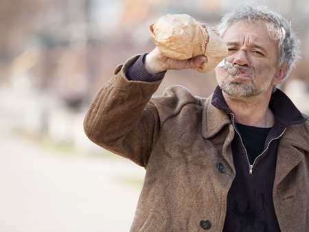 homeless man: Homeless man drinking. Depressed senior man drinking alcohol on street