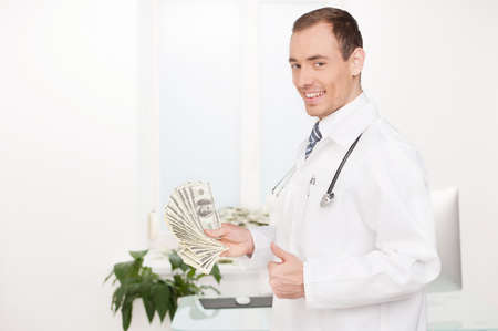 doctor holding money: Doctor with money. Cheerful young male doctor holding paper currency and gesturing