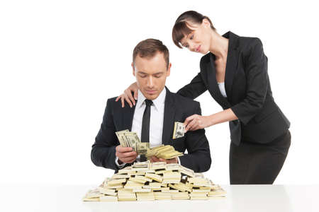 bribing: Bribing. Cheerful young businessman counting money while woman in formalwear putting more money into his pocket