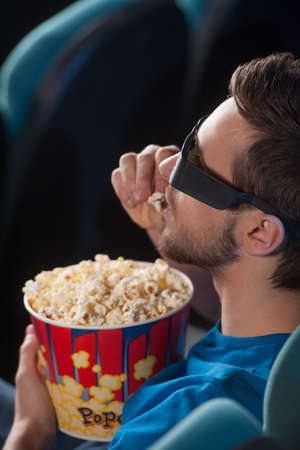 Men at cinema. Top view of excited young men in glasses watching movie at the cinema and eating popcorn photo