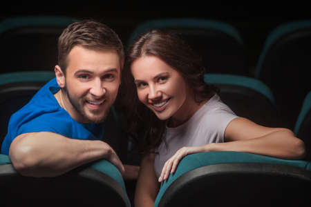 Couple at cinema. Young couple looking over shoulder while sitting at cinema photo