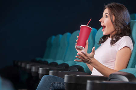 Excited women at the cinema. Side view of beautiful young women drinking soda and gesturing while watching movie at the cinema photo