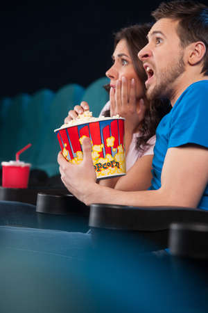 Couple watching horror movie. Side view of terrified people in watching movie at the cinema photo