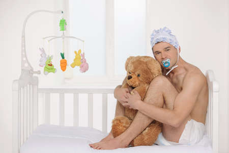 Big baby. Infant adult man in diaper holding teddy bear while sitting on the baby bed