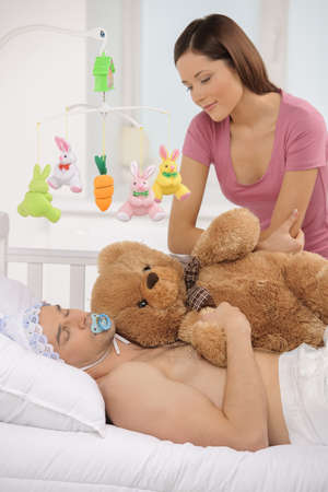 Big baby in bed. Infant adult man lying on the baby bed while young woman looking at him photo