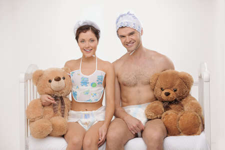 30s adult: Big babies. Two infant young people in baby wear and diapers holding teddy bears and smiling