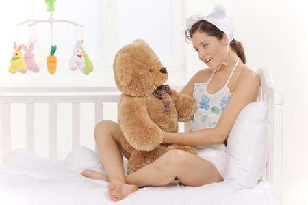pacifier: Bebé grande. Mujer joven en ropa infantil para bebés y pañales sosteniendo osos de peluche y sonriente Foto de archivo