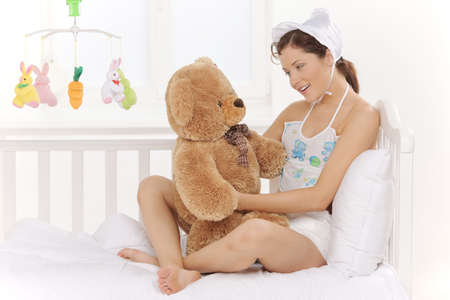 only young adults: Big baby. Infant young woman in baby wear and diapers holding teddy bears and smiling Stock Photo