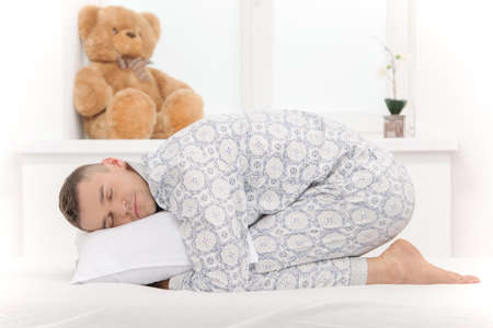 Big baby in pajamas. Side view of infant adult man lying on the baby bed photo