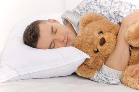 Big baby with Teddy Bear. Infant adult man sleeping with his teddy bear photo