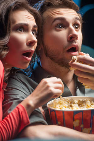 Exciting movie. Close-up of shocked young couple eating popcorn and drinking soda while watching movie at the cinema photo