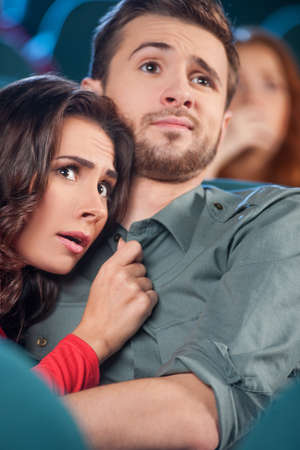 Horror movie. Terrified young couple hugging while watching movie the cinema Stock Photo - 21986219