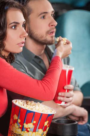 Great movie! Close-up of young couple feeding each other while watching movie at the cinema photo