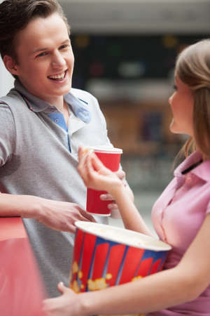 Couple talking. Cheerful young couple drinking soda and eating popcorn photo