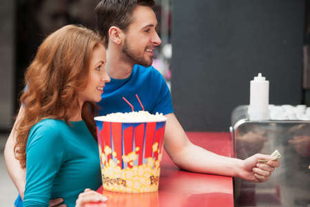 Loving couple in bar. Young loving couple buying popcorn and soda at the cinema bar Stock Photo - 21986250