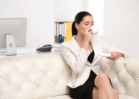 Relaxing in office. Beautiful middle-aged businesswoman sitting on the couch and drinking coffee