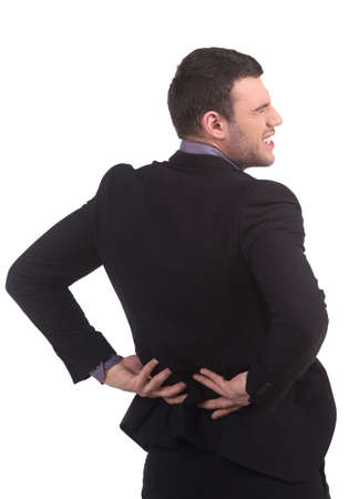 man back pain: Pain in back. Rear view of young man in formalwear holding hands on back while isolated on white