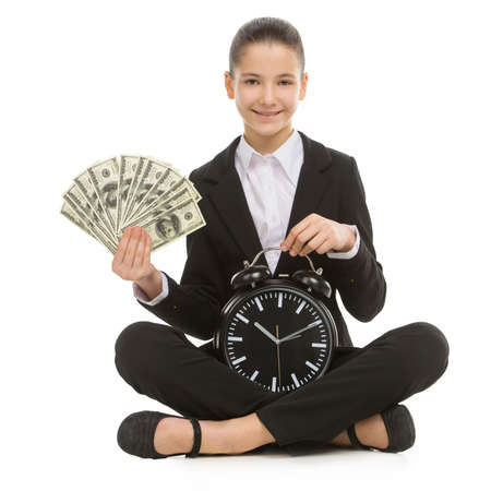 time money: Time is money. Cheerful little girl in formalwear holding watch in one hand and money in another while sitting isolated on white