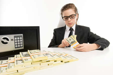 bossy: Counting money  Bossy little boy in formalwear counting money while sitting at his working place Stock Photo