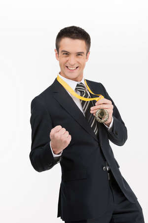 Businessmen with medal. Happy young businessman showing his gold medal while isolated on white photo