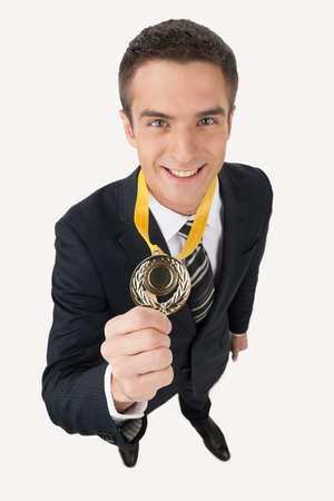 Business award. Top view of happy young businessman showing his gold medal while standing isolated on white photo
