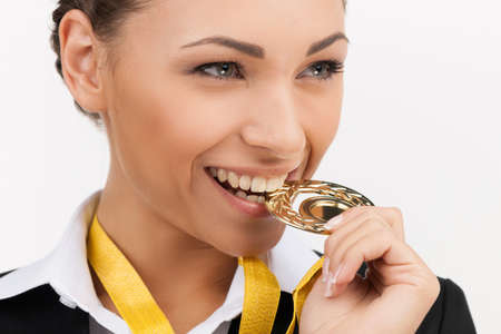 gold medal: Businesswomen with gold medal. Beautiful young businesswomen trying her gold medal by teeth while isolated on white