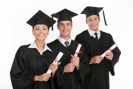 Graduating from the university. Three cheerful young people holding their diplomas and smiling at camera Stock Photo