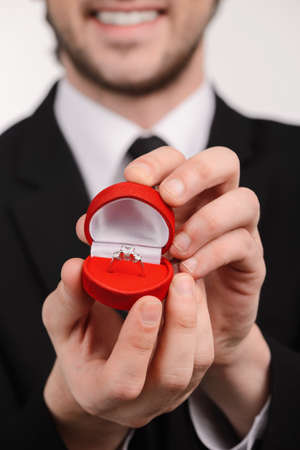 outstretching: Young smiley men in suit holding an open box with engagement ring inside standing against white background Stock Photo