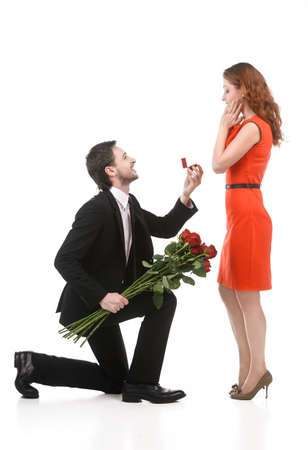 kneeling man: Young man in full suit standing on one knee and making a proposal to his girlfriend against white background Stock Photo