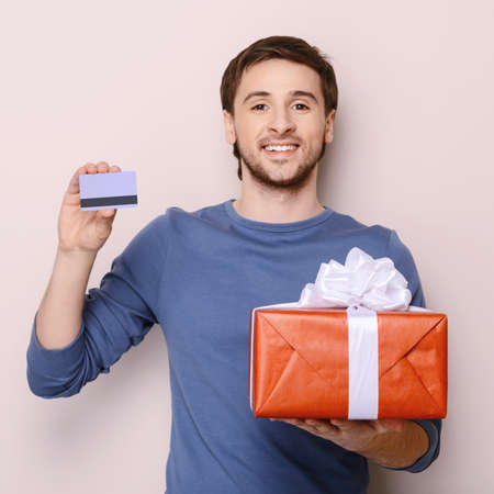 Portrait of young man holding gift box and a credit card. Handsome young smiley man holding a credit card in one hand and a gift box in another one photo