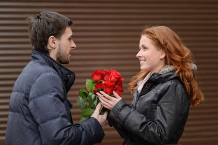 Romantic date. Young man presenting a bunch of red roses to his cute girlfriend photo