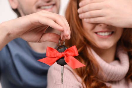 eyes closing: Guess what! Young men closing his girlfriends eyes with one hand and holding a car key in another one Stock Photo