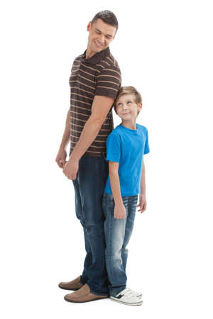 measure height: Father and son. Cheerful father and son standing close to each other and smiling while isolated on white Stock Photo