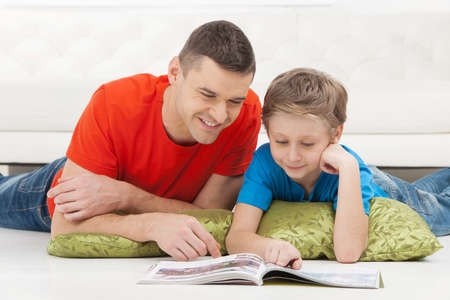 Father and son reading. Cheerful father and son reading magazine together photo