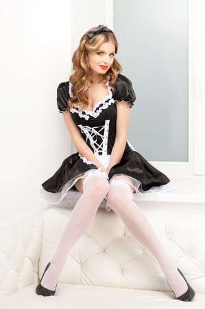 Sexy maid. Beautiful young maid in white pantyhose sitting on the window sill and looking at camera photo