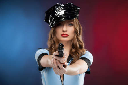 Sexy policewoman. Beautiful young policewoman aiming you with a gun while isolated on colored background photo