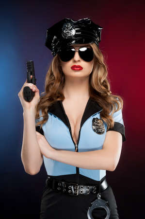Sexy policewoman. Beautiful young policewoman in uniform holding a gun while standing isolated on colored background photo