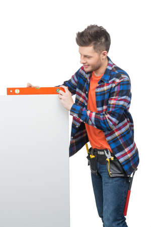 Handyman measuring level. Young confident craftsperson measuring the level with special tool Stock Photo - 22009999