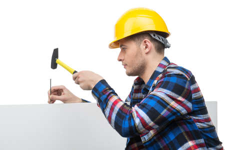 Handyman at work. Confident young handymen using hummer while working Stock Photo - 22020514
