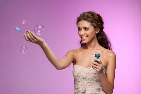 Playing with a bubble wand. Beautiful young women playing with the soap  bubbles while standing isolated on colored background photo