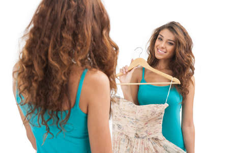 This dress is perfect. Beautiful young women holding a dress and looking at the mirror