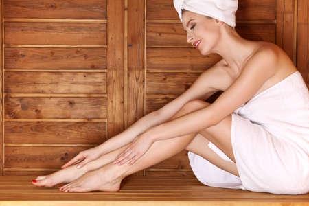 sauna nackt: Frau sitzt auf Holzbank, Entspannung in der Sauna im Kurhaus.