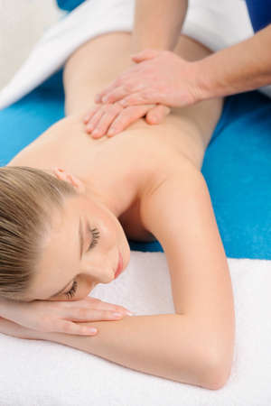 Close-up of a young woman receiving back massage at spa photo