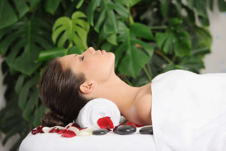Young woman relaxes on a massage table with rose petals. Horizontal shot. photo