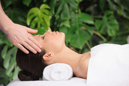 Woman enjoying a wellness head massage in a spa photo