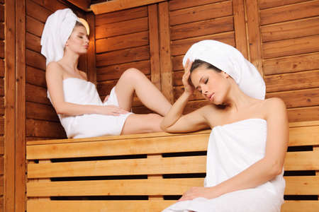woman lying down: Beautiful young females relaxing in wooden spa room, eyes closed