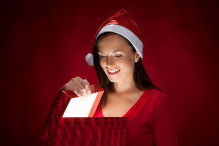Beautiful young woman in Santa hat holding a gift box and looking inside of it while isolated on red photo