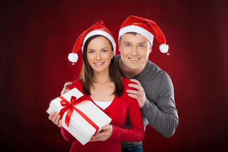 Together at Christmas Eve. Cheerful young couple in Santa hat holding a gift box and smiling while standing isolated on red photo